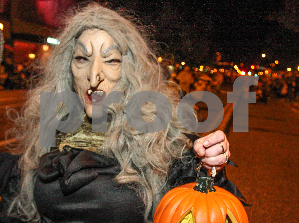 Description of . This ghoulish figure shows off her pumpkin. Photo by Kevin Hoffman, the Mercury