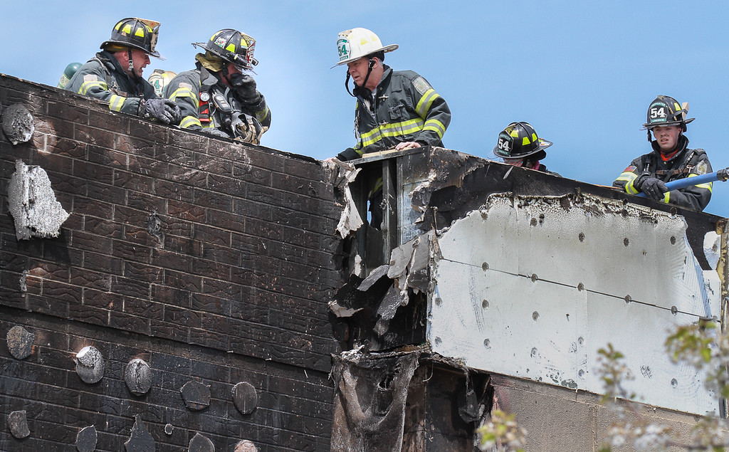 Description of . Firefighters inspect fire damage to wall and rooftop of the Kohl's  store in Royersford. Photo by Kevin Hoffman, The Mercury
