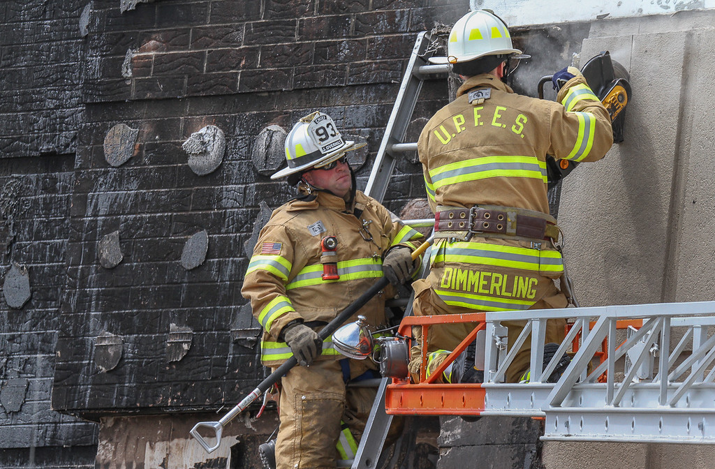 Description of . Firefighters use a saw to cut styrofoam wall covering which ignited at the Kohl's store. Photo by Kevin Hoffman, The Mercury
