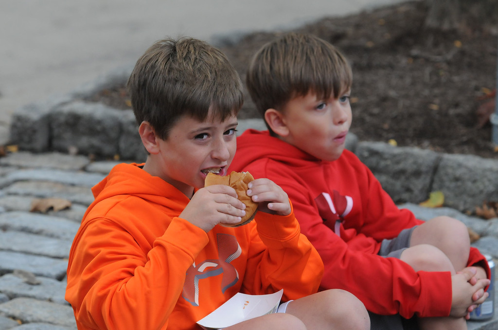 Description of . Josh and Karson Graber munch on hamburgers at the Carousel of Flavor Sunday. Photo by John Strickler/The Mercury