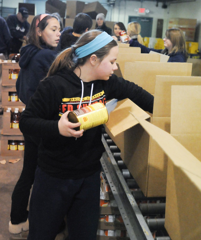 Description of . Pottstown High School and Pope John Paul II students a to pack boxes of food at the Mercury for Operation Holiday delivery. ERin Cannon packs food.Photo by John Strickler/The Mercury
