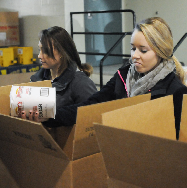 Description of . Pottstown High School and Pope John Paul II students a to pack boxes of food at the Mercury for Operation Holiday delivery. Tori Gery and Megan Remick pack food. Photo by John Strickler/The Mercury