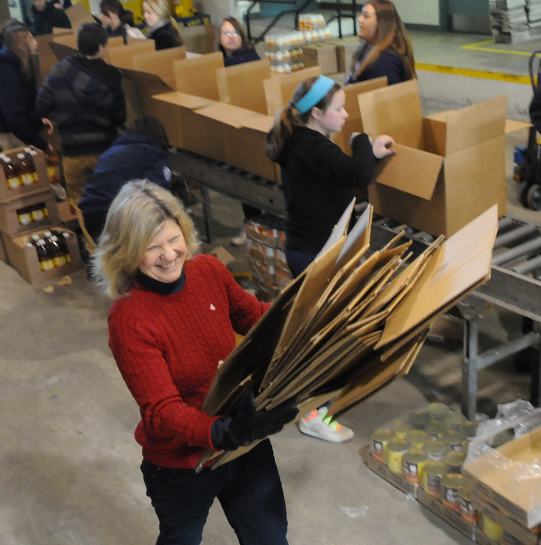 Description of . Mercury editor Nancy March pitches in during Operation Holiday food packing. Pottstown High School and Pope John Paul II students  packed boxes of food at the Mercury for Operation Holiday delivery. Photo by John Strickler/The Mercury