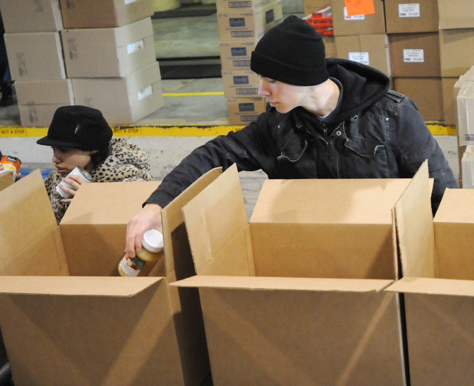 Description of . Naomi Fuerman and Ben Habelcost pack food. Pottstown High School and Pope John Paul II students  pack boxes of food at the Mercury for Operation Holiday delivery. Photo by John Strickler/The Mercury