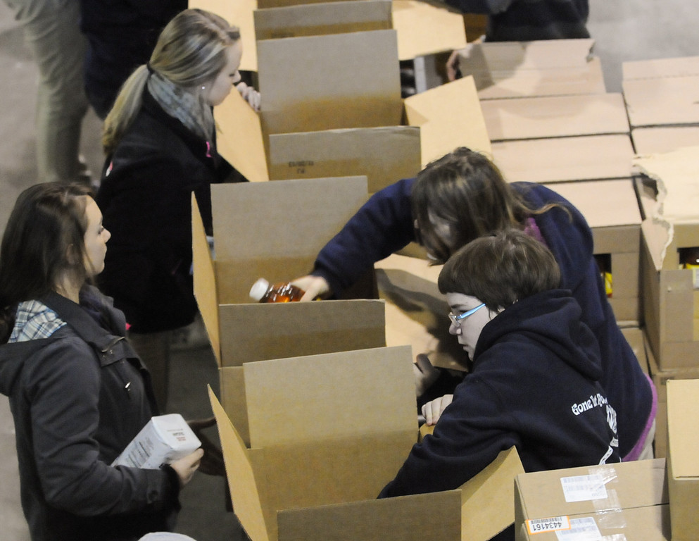 Description of . Pottstown High School and Pope John Paul II students a to pack boxes of food at the Mercury for Operation Holiday delivery. Photo by John Strickler/The Mercury