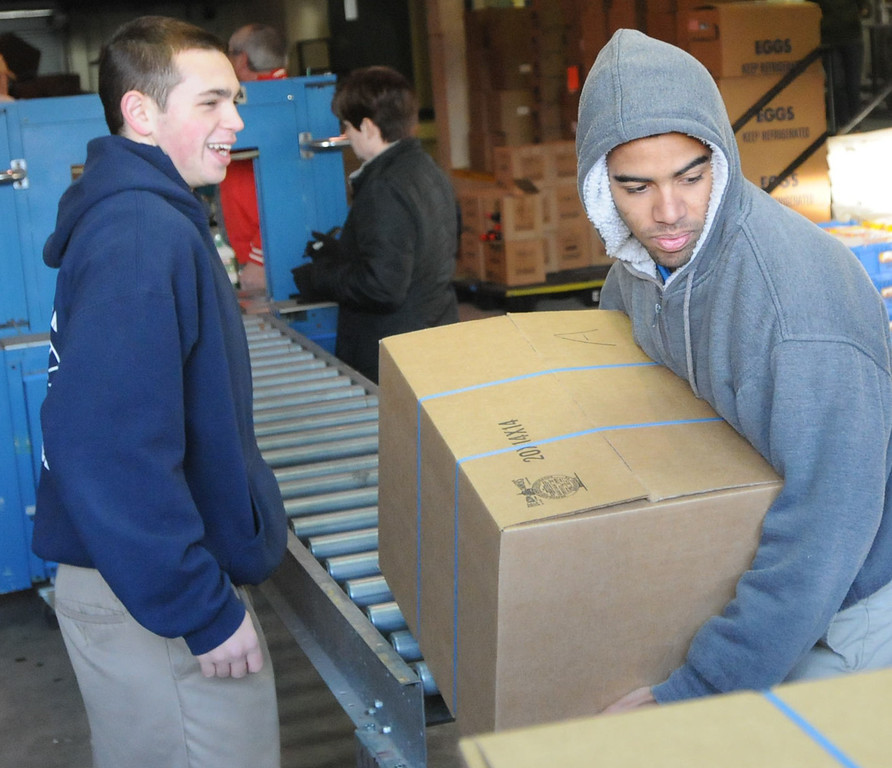 Description of . Pottstown High School and Pope John Paul II students a to pack boxes of food at the Mercury for Operation Holiday delivery. Nate Fuerman and Soloman Bailey load boxes of food. Photo by John Strickler/The Mercury