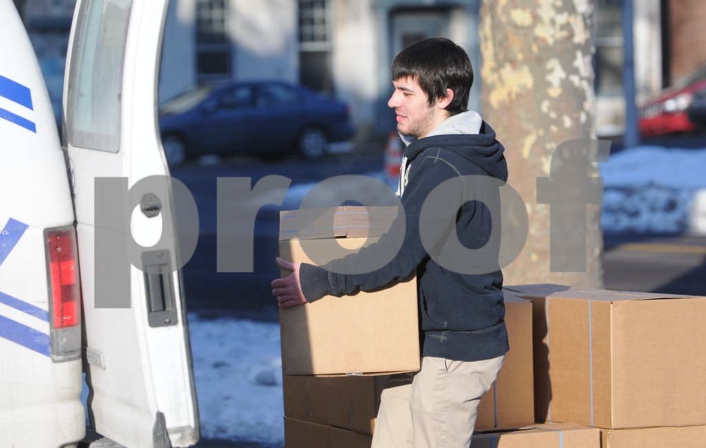 Description of . Pottstown High School and Pope John Paul II students  pack boxes of food at the Mercury for Operation Holiday delivery. Jeff Vontor loads boxes onto Mercury vans.Photo by John Strickler/The Mercury