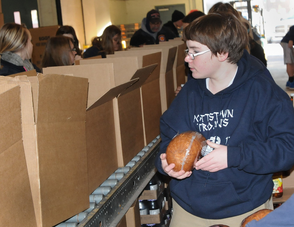 Description of . Pottstown High School and Pope John Paul II students a to pack boxes of food at the Mercury for Operation Holiday delivery. Dylan Brandt packs boxes of food.  Photo by John Strickler/The Mercury