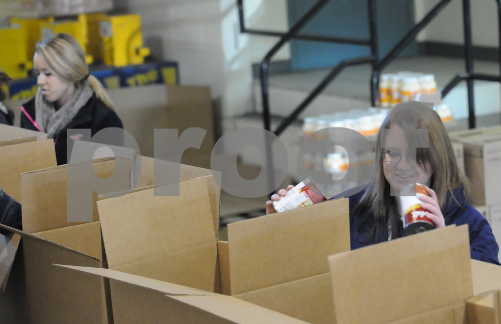 Description of . Pottstown High School and Pope John Paul II students  pack boxes of food at the Mercury for Operation Holiday delivery. Megan Remick and Kelly O'Donnell pack food. Photo by John Strickler/The Mercury