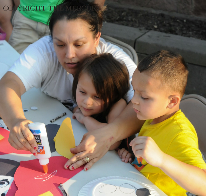 Description of . Melissa Caballero and her children Jade and Ethan Caballero work on a craft making a dalmatian wearing a fire helmet as part of the 'Fire and Ice' National Night Out event at First United Church of Christ on High Street along with Goodwill Fire Co. Photo by John Strickler The Mercury