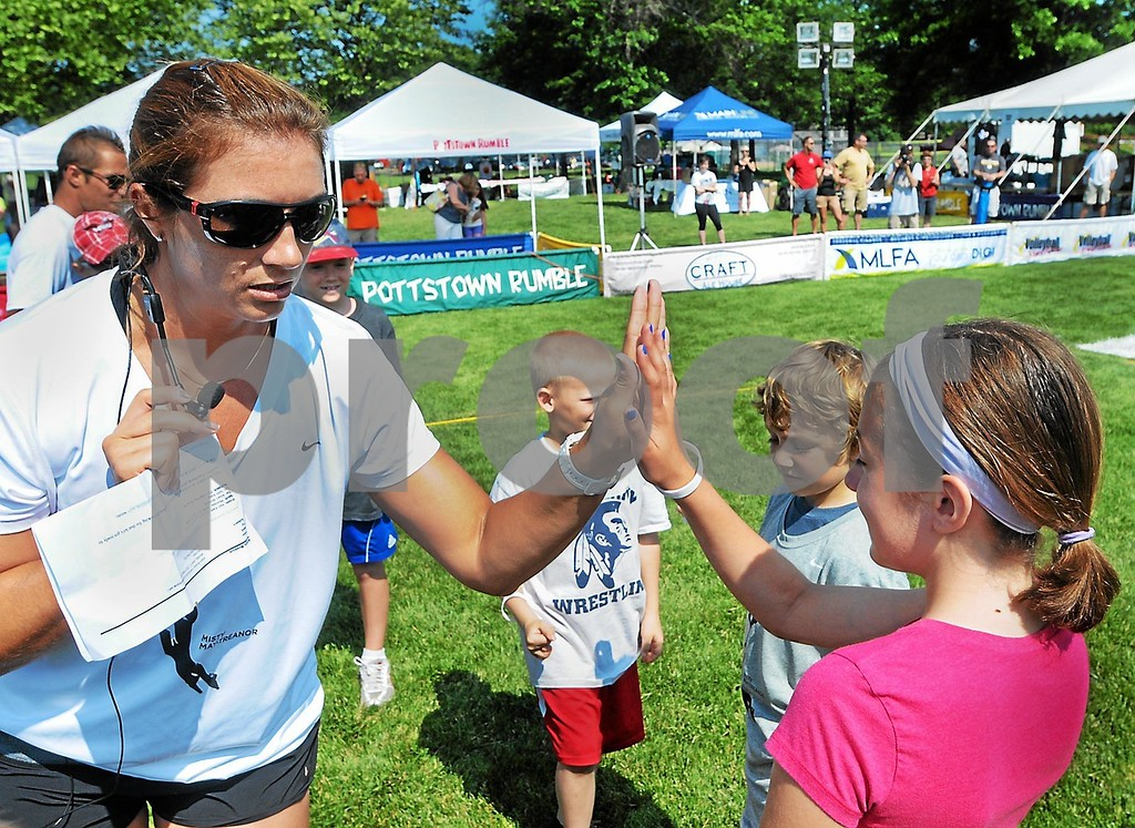 Description of . Misty May-Treanor gives out high fives to kids during a volleyball clinic Thursday, June 20, 2013, at Memorial Park in Pottstown. (Photo by John Strickler/The Mercury)