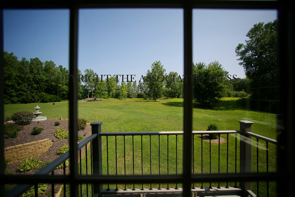 Description of . This is the view of an expansive backyard from inside a luxury home on Wednesday, July 30, 2014, in Springfield, Ill. The home is located near The Rail Golf Course, on the 5 acres of land, next to 66 acres of recreation zoned land and timber. (AP Photo/Seth Perlman)