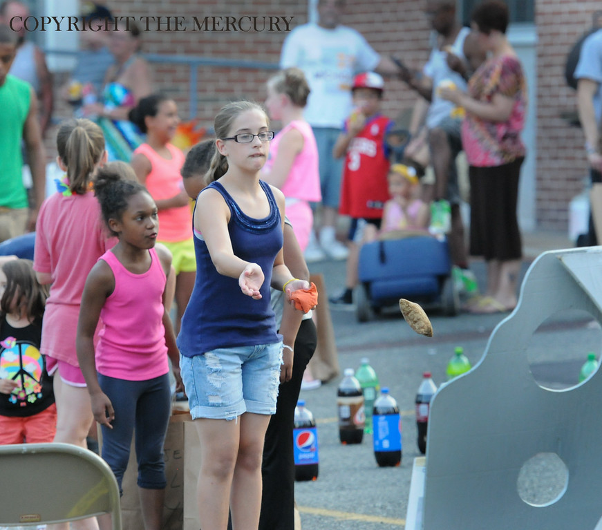 Description of . Kids toss bean bags at First Church of the Brethren at Fifth and York street as part of the National Night Out events held in Pottstown. Photo by John Strickler The Mercury