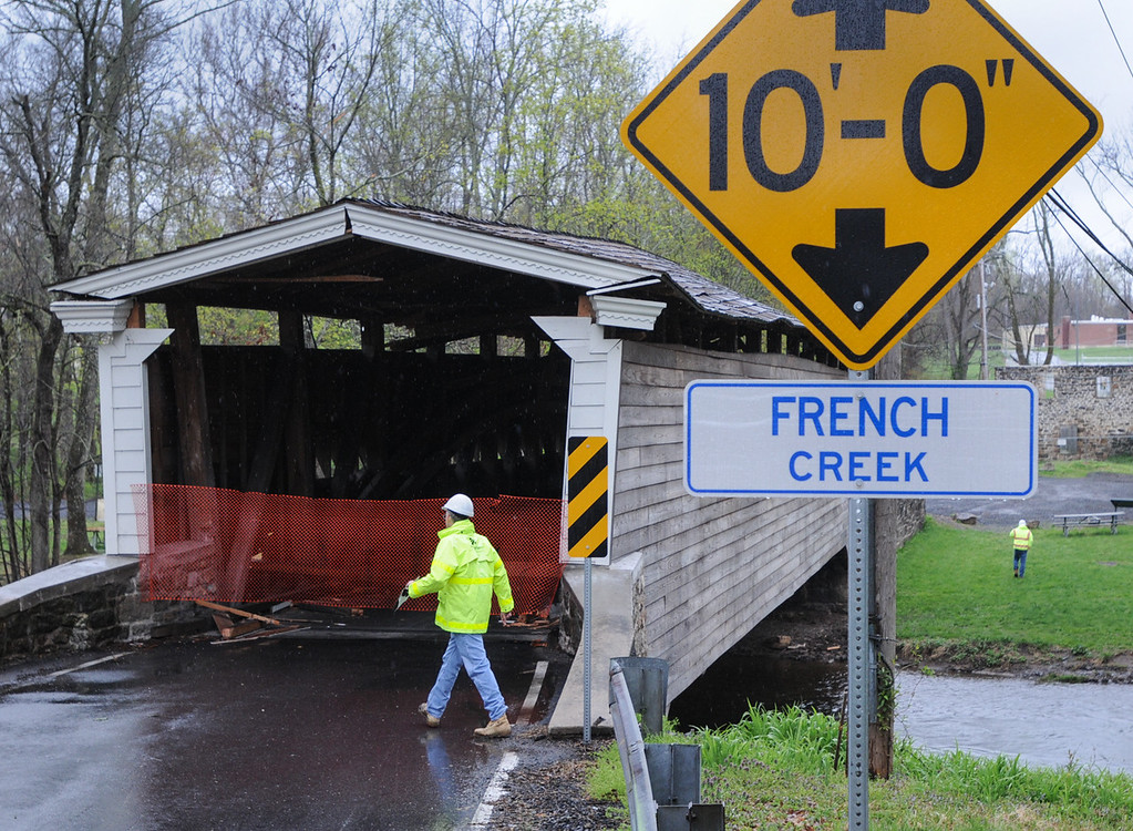 Description of . Officials inspect the Rapps Dam Bridge in East Pikeland Township Tuesday afternoon after the operator of a tractor trailer drove his truck through the covered bridge causing structural damage to beams and the roof. The sign at right shows the height of the bridge at 10 feet. Photo by John Strickler The Mercury