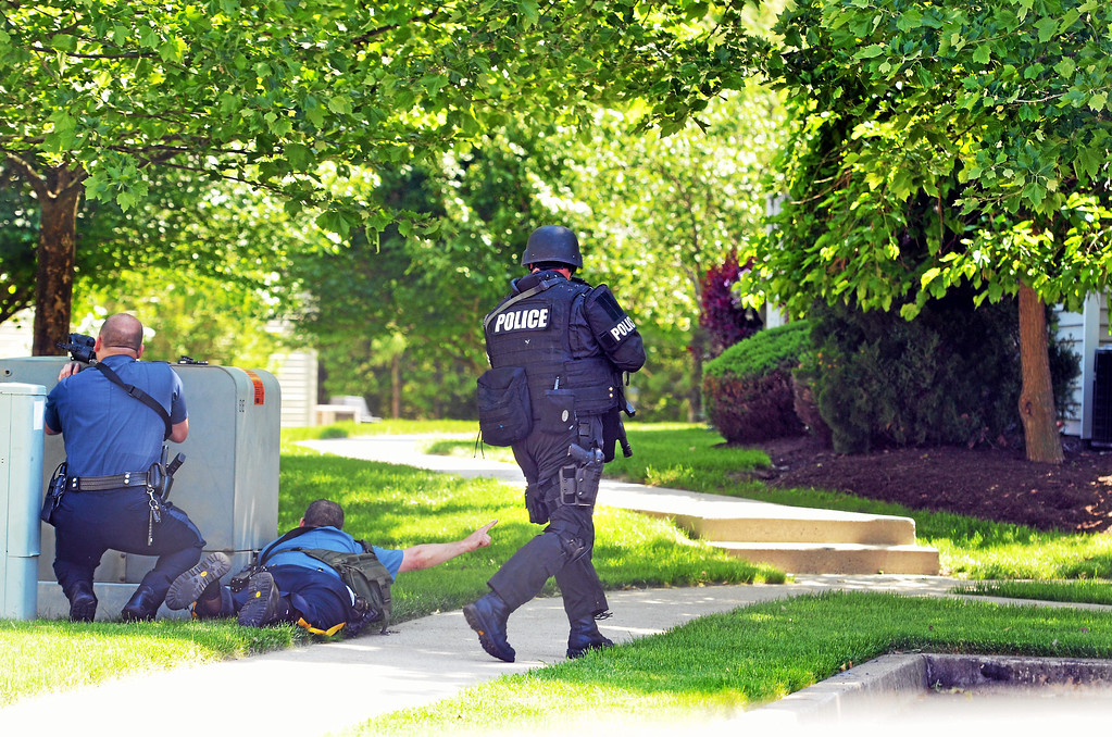 Description of . Responding  police officers take postions near a Harvard Drive home in Montgomery Township following a shooting Monday, June 2, 2014. (Photo by Geoff Patton/The Reporter)