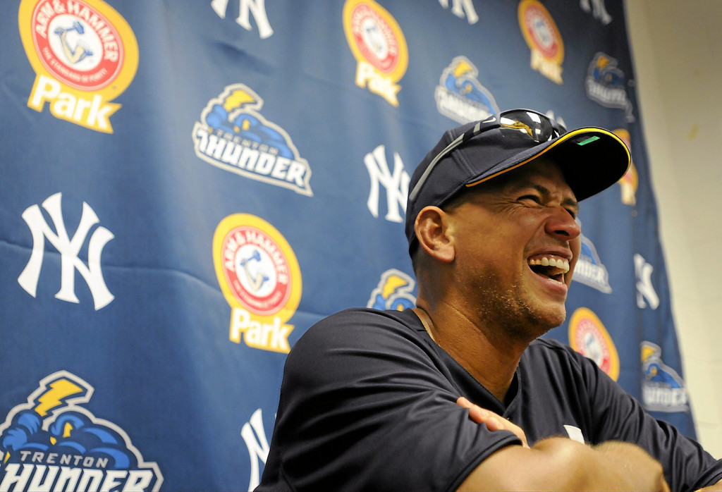 Description of . New York Yankees' Alex Rodriguez laughs during a Class AA minor league baseball pregame news conference, Monday, July 15, 2013, with the Trenton Thunder against the Reading Phillies in Reading, Pa. Rodriguez is doing a rehab assignment with the Thunder recuperating from hip surgery. (AP Photo/Reading Eagle, Jeremy Drey)