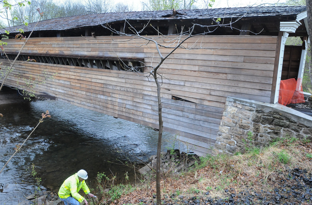 Description of . Officials inspect the Rapps Dam Bridge in East Pikeland Township Tuesday afternoon after the operator of a tractor trailer drove his truck through the covered bridge causing structural damage to beams and the roof. Photo by John Strickler The Mercury