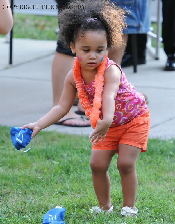 Description of . Two year old Sophia Carter tries to toss bean bags at Trinity U.C.C. at National Night Out. Photo by John Strickler The Mercury