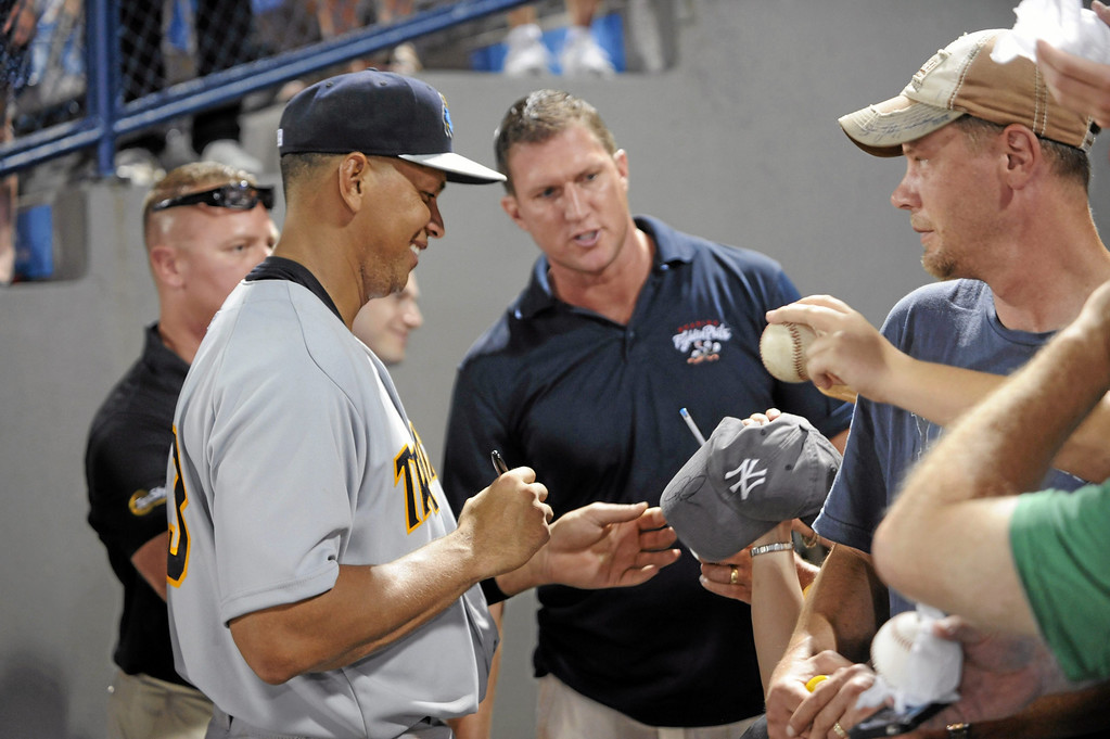 Description of . New York Yankees third baseman Alex Rodriguez, left, signs autographs after a Class AA baseball game with the Trenton Thunder against the Reading Phillies, Monday, July 15, 2013 in Reading, Pa. Rodriguez is doing a rehab assignment with the Thunder recuperating from hip surgery. (AP Photo/Bradley C Bower)