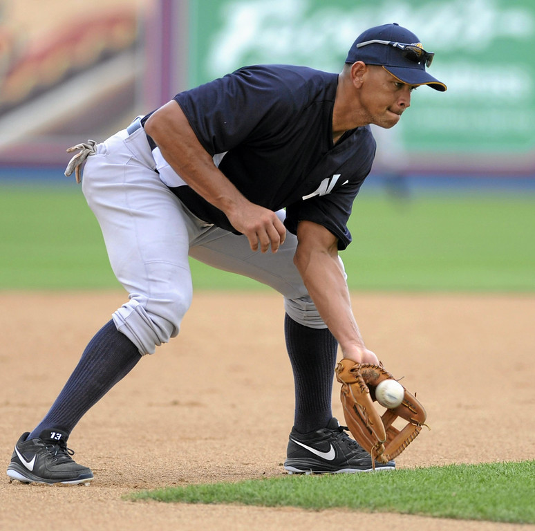 Description of . New York Yankees third baseman Alex Rodriguez fields round balls during batting practice prior to a Class AA baseball game with the Trenton Thunder against the Reading Phillies, Monday, July 15, 2013, in Reading, Pa. Rodriguez is doing a rehab assignment with the Thunder recuperating from hip surgery. (AP Photo/Bradley C Bower)