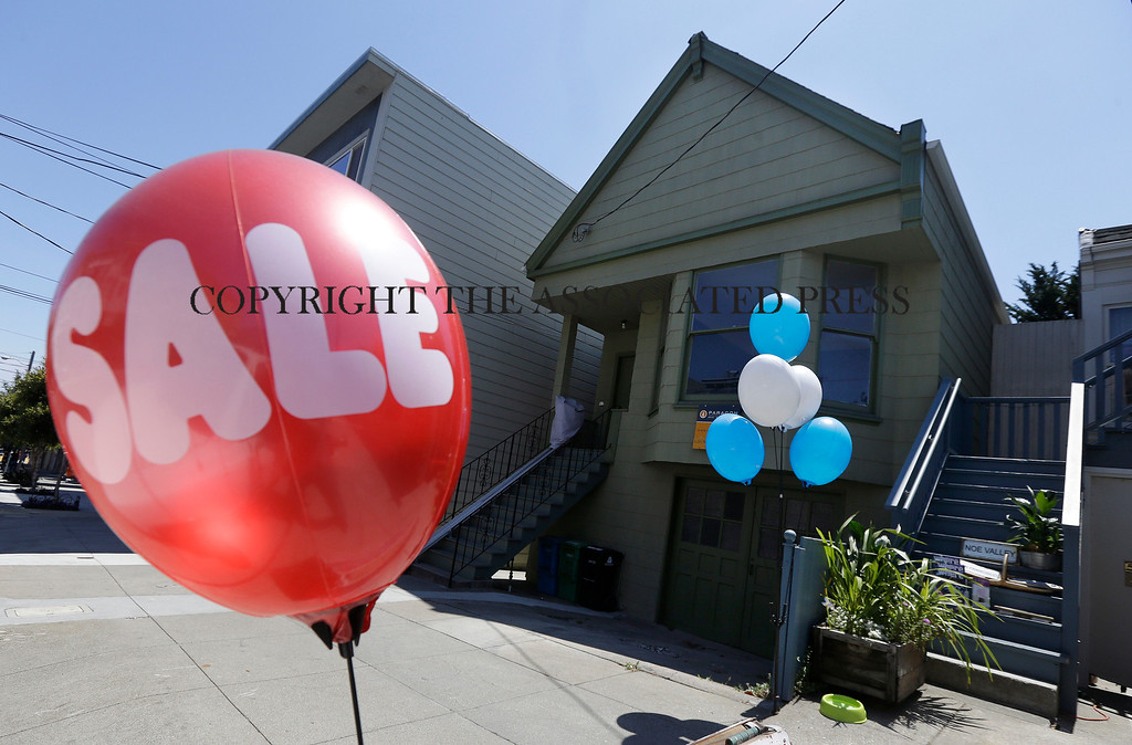 Description of . A sale balloon for a nearby store is shown next to a property in the Noe Valley neighborhood just sold for $1.8 million in cash, $600,000 more than its asking price, in San Francisco, Wednesday, July 30, 2014. In the souped-up world of San Francisco real estate, where the median selling price for homes and condominiums hit seven figures for the first time last month, the cool million that would fetch a mansion on a few acres elsewhere will now barely cover the cost of an 800-square-foot starter home. (AP Photo/Jeff Chiu)