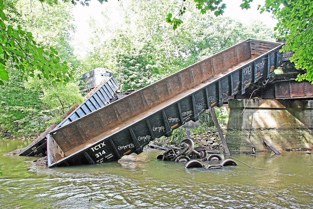 Description of . Two cars lie partway off a bridge in the Brandywine Creek following a train derailment in Valley on Monday, July 8, 2013.
