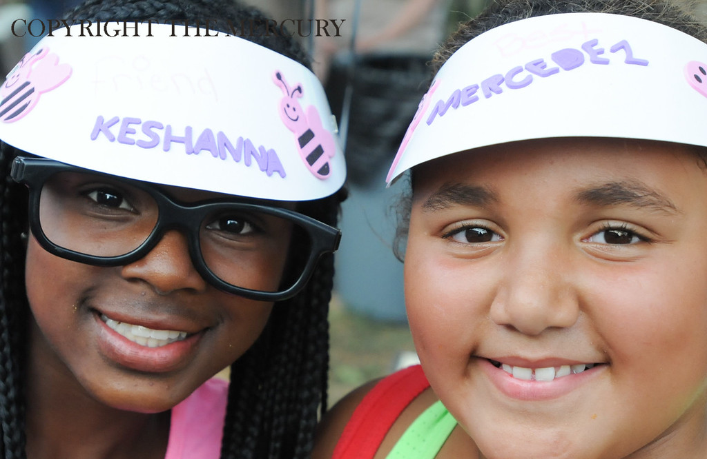 Description of . Keshanna Brown and Mercedez Roye wear hats they made as part of the NAtional Night Out event Chestnut Street Park sponsored by the Victory Christian Life Center and Genesis Housing Inc. Photo by John Strickler The Mercury