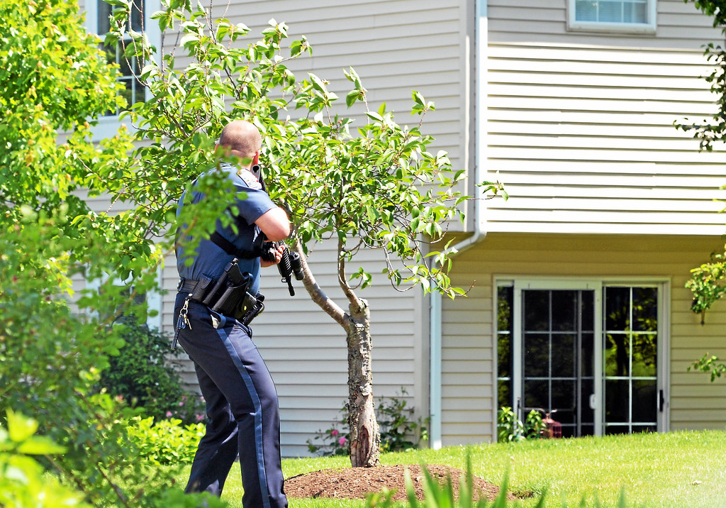 Description of . An armed police officer walks near a residence on Harvard Drive, Montgomery Township, Pa., on Monday, June 2, 2014.  A woman was shot and the alleged shooter was found dead inside a home. (Photo by Geoff Patton/The Reporter)