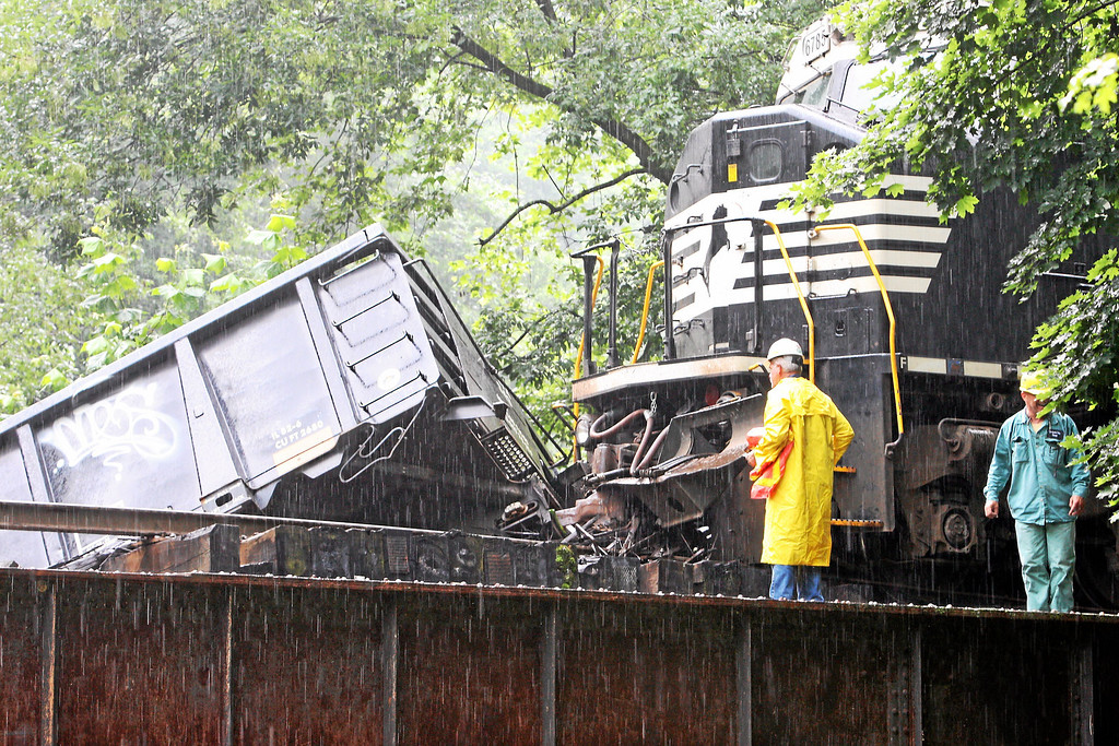 Description of . Workers look over as two cars go off a bridge into the Brandywine Creek following a train derailment in Valley, Chester County, on Monday, July 8, 2013.