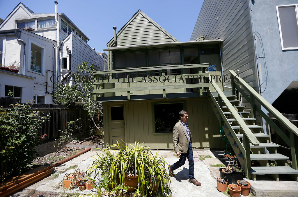 Description of . George Limperis, a realtor with Paragon Real Estate Group, walks in the backyard of a property in the Noe Valley neighborhood in San Francisco, Wednesday, July 30, 2014. In the souped-up world of San Francisco real estate a $1 million will barely cover the cost of an 800-square-foot starter home that needs work and may or may not include private parking. (AP Photo/Jeff Chiu)