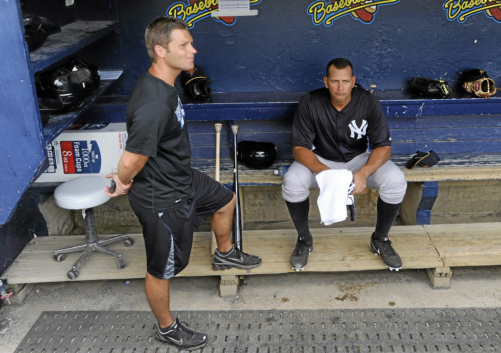Description of . New York Yankees third baseman Alex Rodriguez, right, sits in the dugout takling with Yankee athletic trainer Mike Wickland, left, before batting practice in a Class AA baseball game with the Trenton Thunder against the Reading Phillies, Monday, July 15, 2013, in Reading, Pa. Rodriguez is doing a rehab assignment with the Thunder recuperating from hip surgery. (AP Photo/Bradley C Bower)