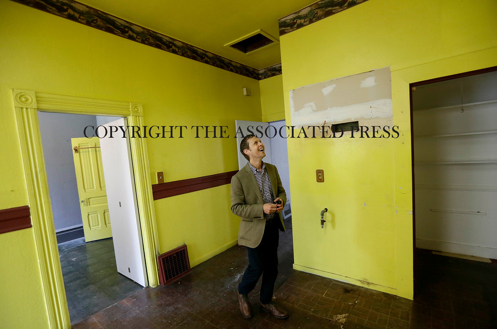 Description of . George Limperis, a realtor with Paragon Real Estate Group, smiles as he walks through the kitchen of a property that was recently sold in the Noe Valley neighborhood in San Francisco, Wednesday, July 30, 2014. (AP Photo/Jeff Chiu)