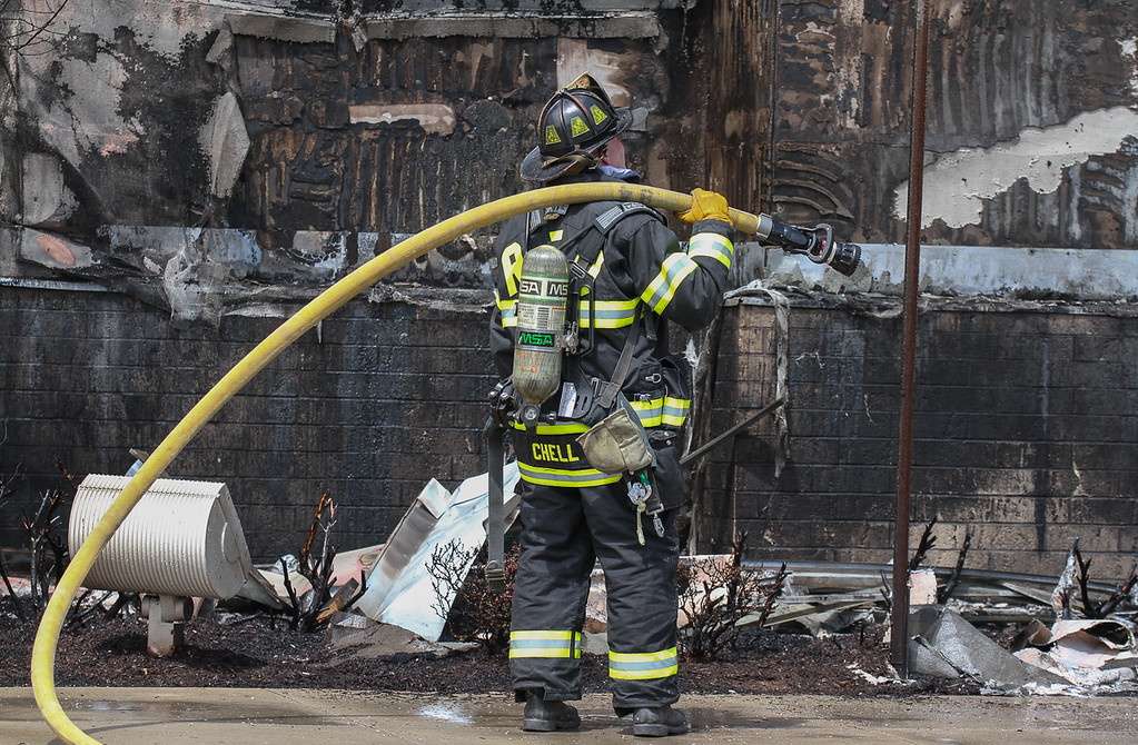 . A lone firefighter stands by burned wall outside the Kohls store in Royersford. Photo by Kevin Hoffman, The Mercury