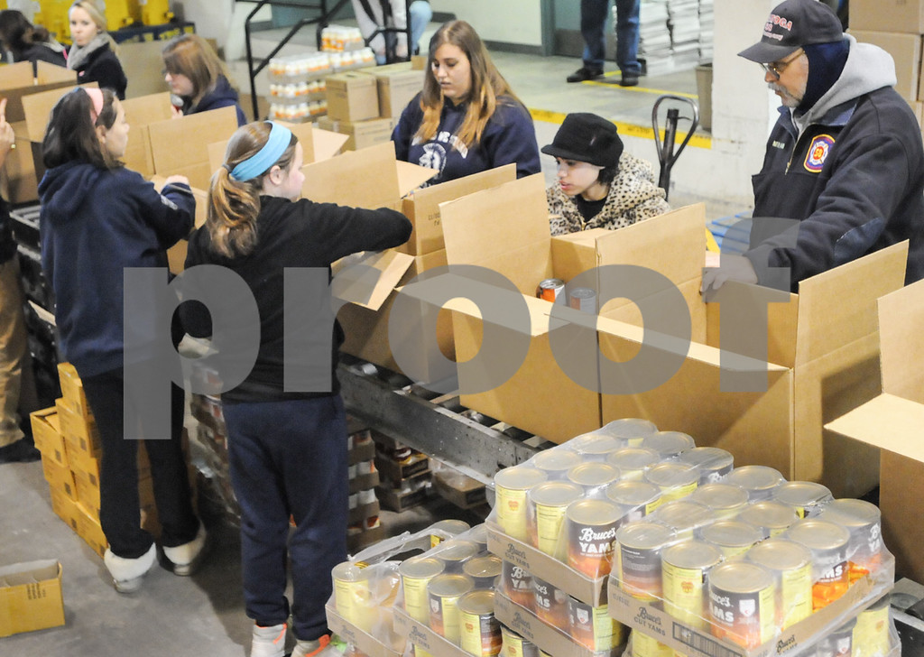 . Pottstown High School and Pope John Paul II students a to pack boxes of food at the Mercury for Operation Holiday delivery. Photo by John Strickler/The Mercury