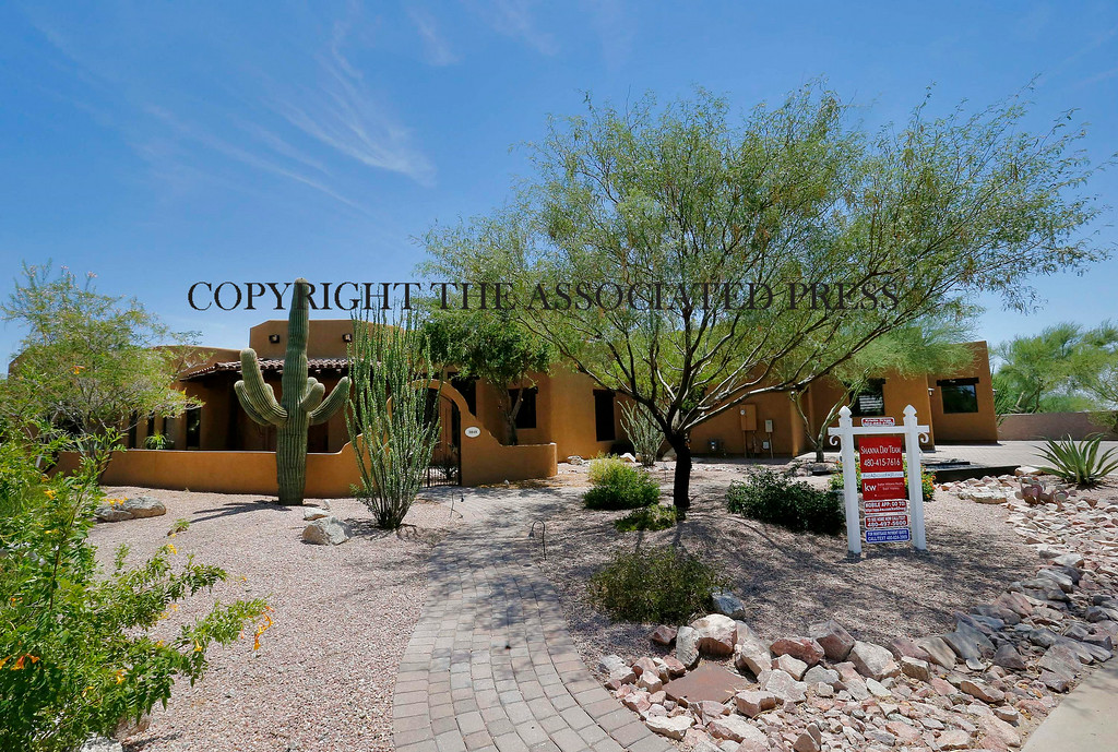 . A luxury home with a listing price of $1 million is shown on Wednesday, July 30, 2014, in the Las Sendas community of Mesa, Ariz. The more than 4,000-square-foot home has a desert view on a golf course in the Phoenix suburb as well as a four car garage. (AP Photo/Matt York)