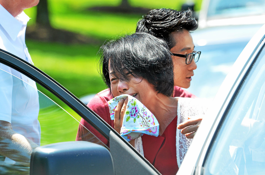 . A man and woman who were prevented by police from approaching the scene of a shooting on Harvard Drive in Montgomery Township are escorted from the area visibly upset  Monday, June 2, 2014. (Photo by Geoff Patton/The Reporter)